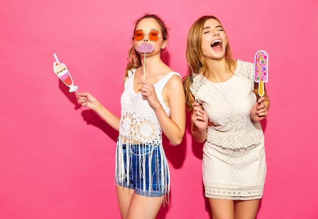 Dwie młode stylowe uśmiechnięte blond kobiety jedzące rekwizyty słodkie lody i fałszywy koktajl. pozytywne modele w letnich ubraniach hipster pozowanie w pobliżu różowej ściany w okularach przeciwsłonecznych