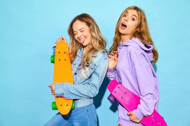 Dwie młode stylowe uśmiechnięte blond kobiety z deskorolkami grosza. kobiety w lecie hipster sportowe ubrania pozowanie w pobliżu niebieską ścianą. pozytywne modele