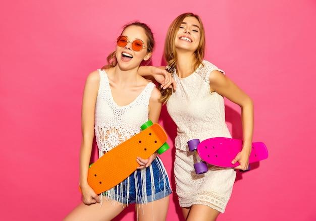 Dwie młode stylowe uśmiechnięte blond kobiety z deskorolkami grosza. modele w letnie hipster białe ubrania pozowanie w pobliżu różowe ściany w okularach przeciwsłonecznych. pozytywna kobieta
