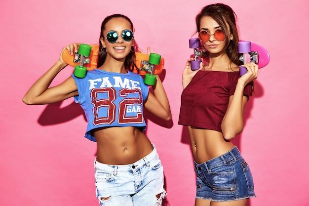 Dwie młode stylowe uśmiechnięte kobiety brunetka z grosza deskorolki. modele w letnie hipster sportowe ubrania pozowanie w pobliżu różowe ściany w okularach przeciwsłonecznych. pozytywna kobieta