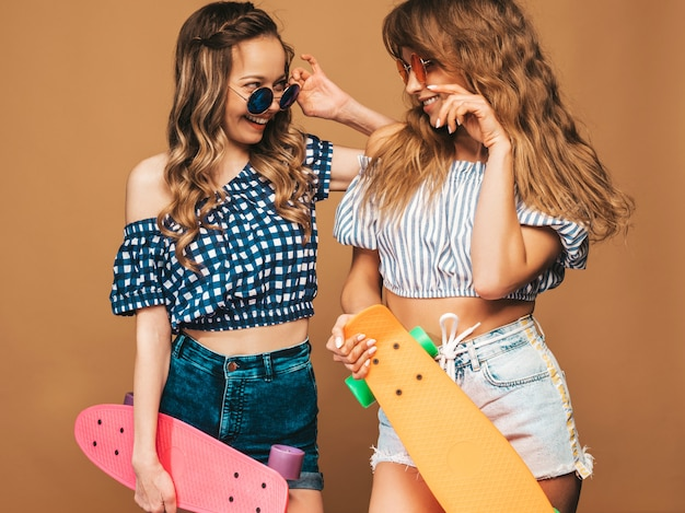 Dwie młode stylowe uśmiechnięte piękne dziewczyny z kolorowymi deskorolkami grosza. kobiety w lecie pozowanie ubrania kraciaste koszule. pozytywne modele zabawy