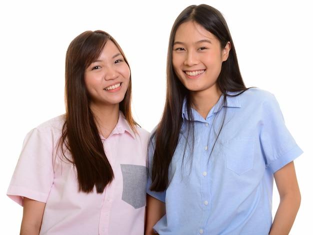 Dwie młode szczęśliwe azjatyckie nastolatki z uśmiechem