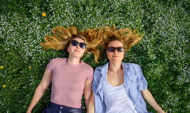 Dwie młode szczęśliwe dziewczyny z długimi włosami leżą na zielonej trawie w letni dzień i uśmiechają się do kamery