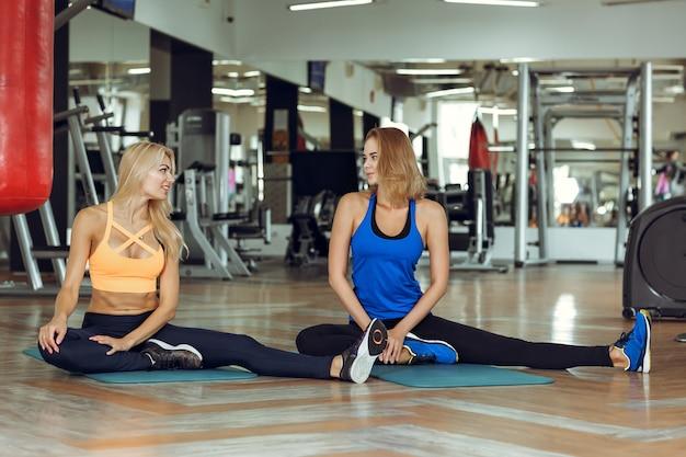 Dwie młode szczupłe blond kobiety robiące ćwiczenia na siłowni