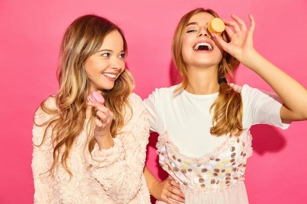 Dwie młode urocze piękne uśmiechnięte kobiety hipster w modne letnie ubrania. kobiety z kolorowymi makaronikami, trzymające macarony blisko twarzy. pozowanie na różowej ścianie