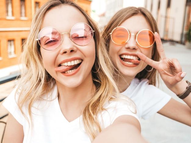 Dwie młode uśmiechnięte hipster blond kobiety w letnie białe ubrania ubrania. dziewczyny robienia zdjęć autoportretów selfie na smartfonie. kobieta pokazuje znak pokoju i język