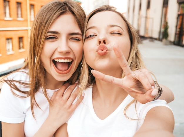 Dwie młode uśmiechnięte hipster blond kobiety w letnie ubrania. dziewczyny robienia zdjęć autoportretów selfie na smartfonie. .