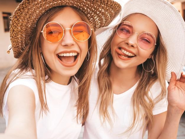 Dwie młode uśmiechnięte hipster blond kobiety w letniej białej koszulce. dziewczyny, biorąc selfie autoportret zdjęcia na smartfonie. modele pozowanie na tle ulicy. kobieta pokazuje język i pozytywne emocje