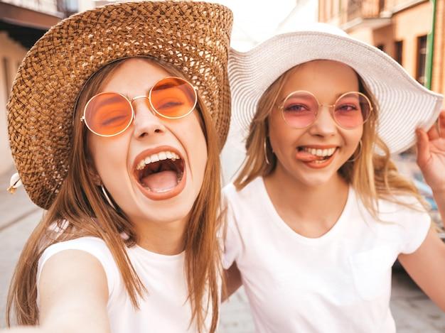 Dwie młode uśmiechnięte hipster blond kobiety w letniej białej koszulce. dziewczyny, robiąc selfie autoportret zdjęcia na smartfonie. modele pozowanie na tle ulicy. kobieta pokazuje pozytywne emocje
