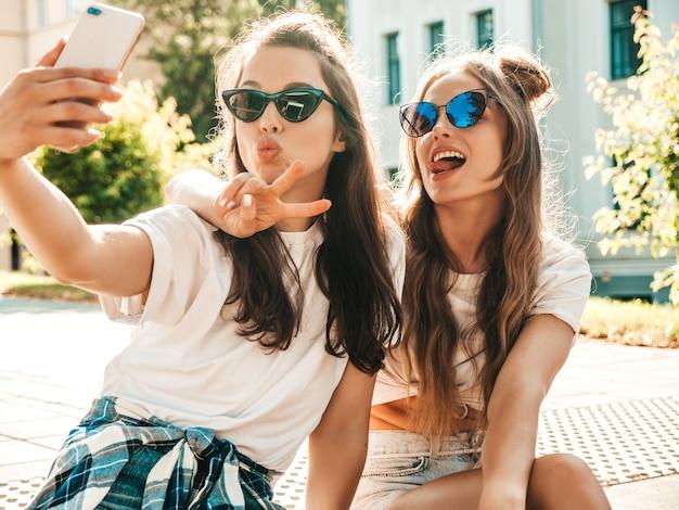 Dwie młode uśmiechnięte hipsterki w letnich ubraniach