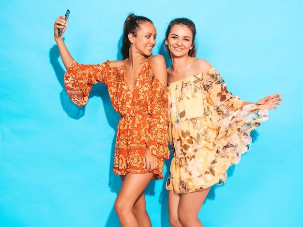 Dwie młode uśmiechnięte kobiety hipster w letnich sukienkach hippie. dziewczyny biorące selfie autoportret zdjęcia na smartfonie. modele pozowanie w pobliżu niebieską ścianą w studio