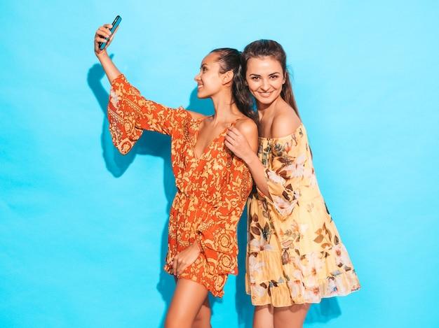 Dwie młode uśmiechnięte kobiety hipster w letnie sukienki hippie. dziewczyny biorące selfie autoportret zdjęcia na smartfonie. modele pozowanie w pobliżu niebieską ścianą w studio. kobieta pokazująca pozytywne emocje na twarzy