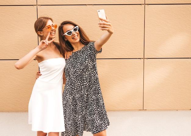 Dwie młode uśmiechnięte kobiety hipster w letnie ubrania.