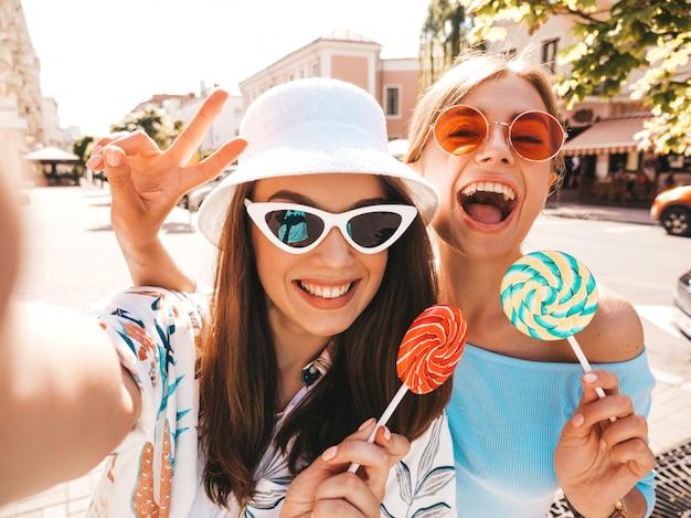 Dwie młode uśmiechnięte modniś kobiety w przypadkowym lecie odziewają.