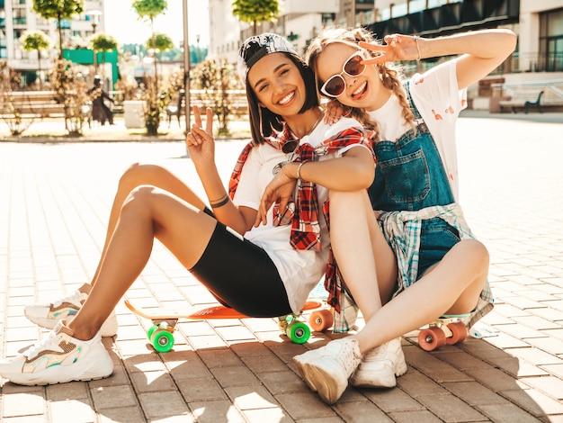 Dwie młode uśmiechnięte piękne dziewczyny z kolorowymi deskorolkami grosza. kobiety w letnie ubrania hipster siedzi na tle ulicy. pozytywne modelki bawią się i wariują. pokazuje znak pokoju