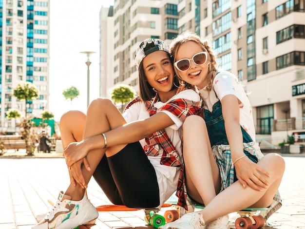 Dwie młode uśmiechnięte piękne dziewczyny z kolorowymi deskorolkami grosza. kobiety w letnie ubrania hipster siedzi na tle ulicy. pozytywne modelki bawią się i wariują. pokazywanie języków