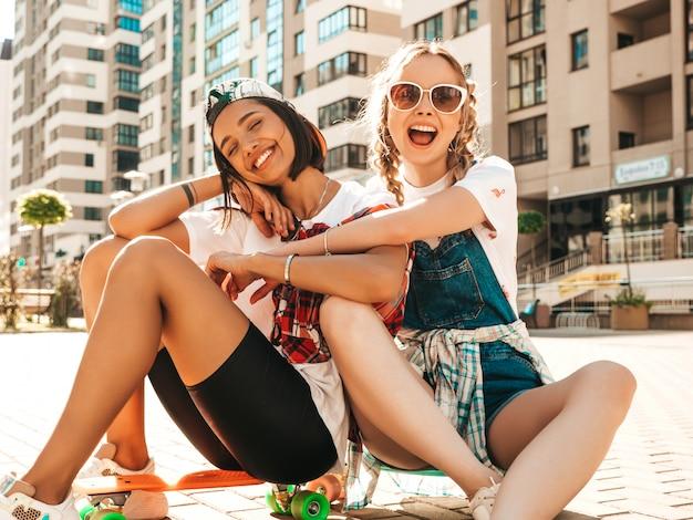 Dwie młode uśmiechnięte piękne dziewczyny z kolorowymi deskorolkami grosza. kobiety w letnie ubrania hipster siedzi na tle ulicy. pozytywne modelki bawią się i wariują