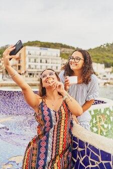Dwie młode wesołe hiszpanki robią sobie selfie i jedzą lody