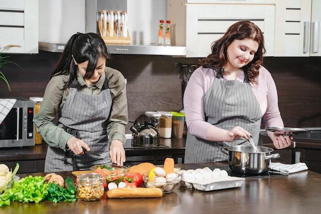 Dwie młode, wesołe koleżanki, przygotowujące wspólnie posiłek w domowej kuchni.