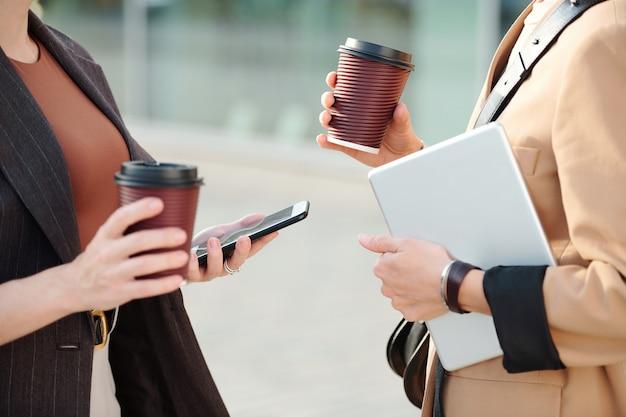 Dwie młode współczesne kobiety biznesu z napojami i mobilnymi gadżetami stojące naprzeciwko siebie w środowisku miejskim