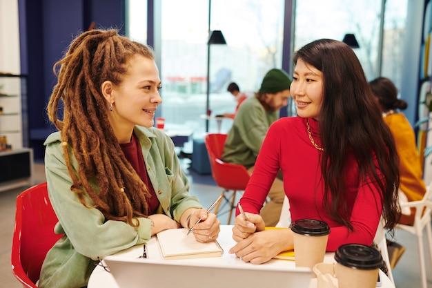 Dwie młode współczesne międzykulturowe kobiety biznesu w casualwear pracujące razem nad prezentacją, siedząc przy biurku w biurze