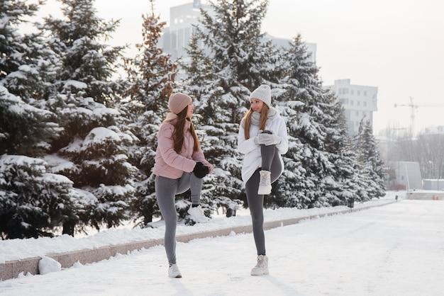 Dwie młode wysportowane dziewczyny rozgrzewają się przed bieganiem w słoneczny zimowy dzień. zdrowy styl życia.