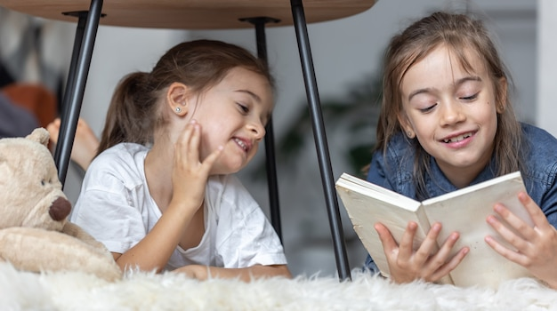 Dwie młodsze siostry dobrze się bawią, czytając razem książkę, leżąc na podłodze w swoim pokoju.