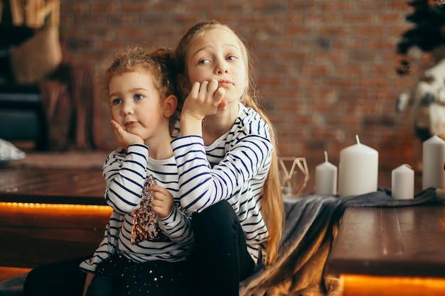 Dwie młodsze siostry rozmawiają siedząc w przytulnym salonie.