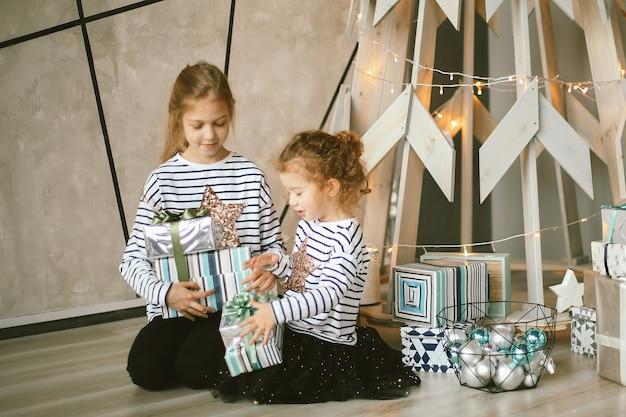 Dwie młodsze siostry siedzące przy stylizowanej choince.