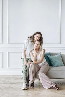 Dwie modelki pozują przy kanapie w studio w nowej kolekcji ubrań