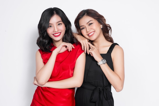 Dwie modne kobiety w ładnych sukienkach stoją razem i dobrze się bawią