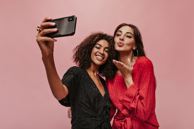 Dwie modne przyjaciółki z ciemnymi włosami w modne ubrania w kropki robią selfie, uśmiechają się i buzią na różowej ścianie