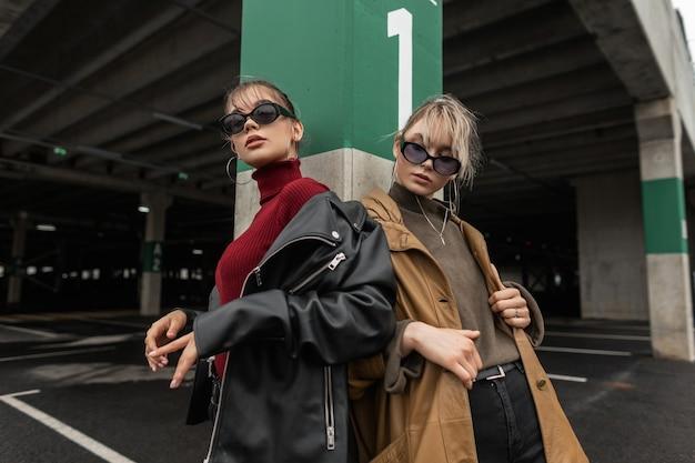 Dwie modne siostry kobiety w stylowych ubraniach ze skórzaną kurtką i swetrem w modnych okularach przeciwsłonecznych pozują w mieście