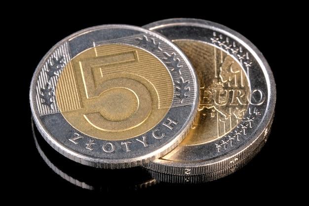 Dwie monety złoty polski i euro z bliska na czarnym tle fotografia makro