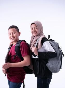 Dwie muzułmańskie uczennice stojące razem, na białym tle, z uśmiechem i radością, siostra i brat przygotowują się do szkoły