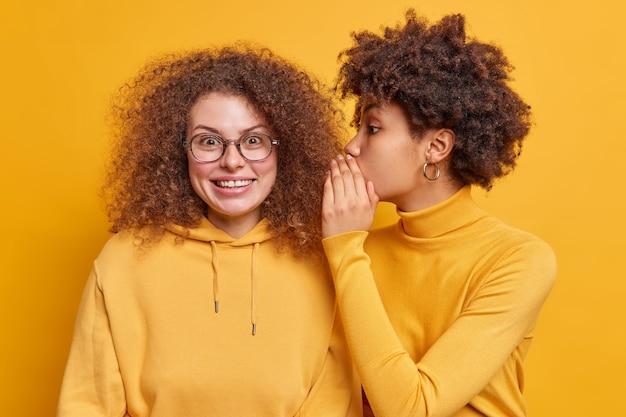 Dwie najlepsze przyjaciółki plotkują ze sobą o tajemnicach. afroamerykanka szepcze plotki do ucha towarzysza, który zaskoczył radosną miną podekscytowaną najnowszymi wiadomościami. koncepcja poufności