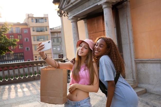Dwie nastolatki robiące selfie po zakupach, trzymając torby