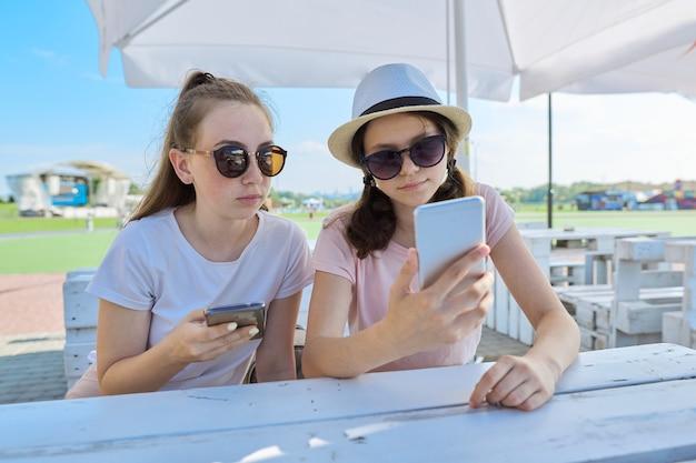Dwie nastolatki ze smartfonami, siedząc i rozmawiając w letniej kawiarni na świeżym powietrzu. młodzież, nastolatki, przyjaźń, komunikacja, koncepcja ludzi