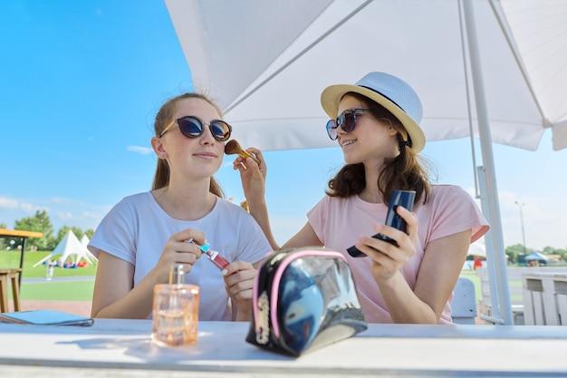 Dwie nastoletnie dziewczyny, makijaż, siedząc w letniej kawiarni na świeżym powietrzu