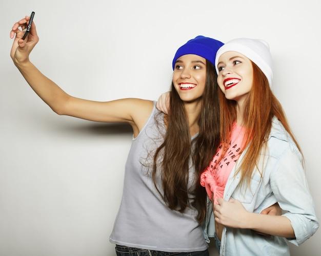 Dwie nastoletnie dziewczyny przyjaciółki w stroju hipster zrobić selfie na telefonie.
