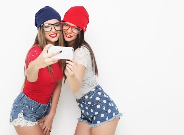 Dwie nastoletnie dziewczyny w stroju hipster zrobić selfie na telefon.