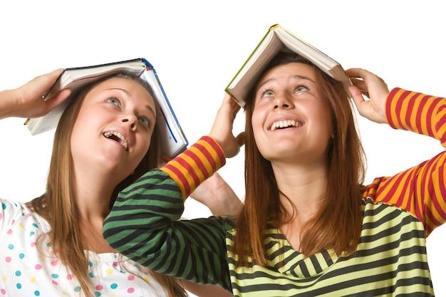 Dwie nastoletnie dziewczyny wygłupią się na białym tle
