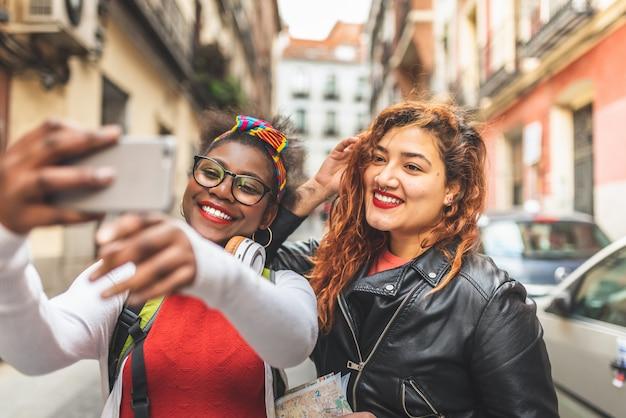 Dwie nastoletnie koleżanki biorąc selfie na zewnątrz