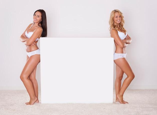 Dwie naturalne dziewczyny pozujące obok tablicy