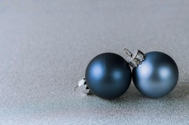 Dwie niebieskie bombki na błyszczącym srebrnym tle świąteczna kompozycja