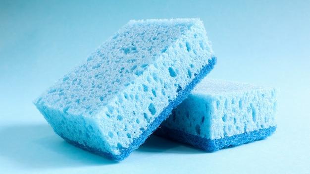 Dwie niebieskie gąbki służące do mycia i ścierania zabrudzeń używane przez gospodynie domowe w życiu codziennym. wykonane są z porowatego materiału, takiego jak pianka. retencja detergentów, która pozwala oszczędnie je wydać.
