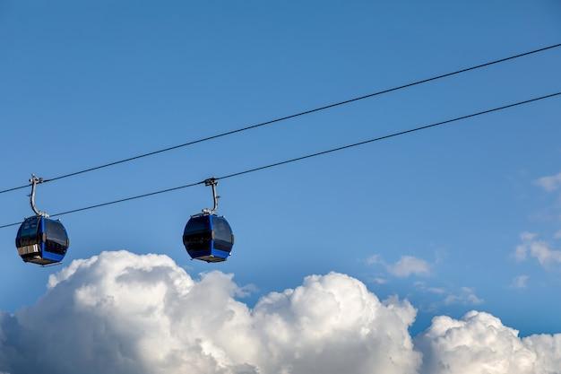 Dwie niebieskie kolejki linowe nad chmurami na tle nieba.