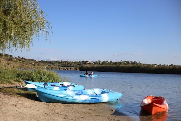 Dwie niebieskie łodzie i jeden pomarańczowy kajak stoją na piaszczystym brzegu rzeki. para robi kajakarstwo na rzece w letni dzień
