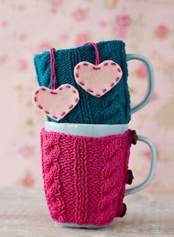 Dwie niebieskie miseczki w niebiesko-różowym swetrze z filcowymi sercami
