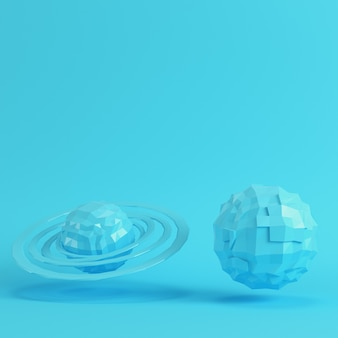 Dwie niebieskie planety low poly na jasnym niebieskim tle